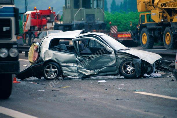 A small passenger car is crushed in this violent accident