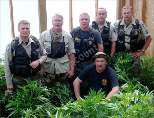 Drug Enforcement Unit of Humboldt County Sheriff's Office poses in a pot-filled greenhouse