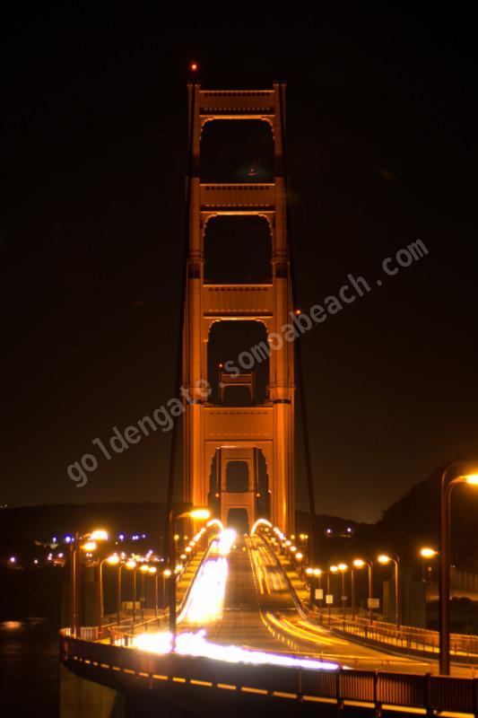 Traffic flows across San Francisco's Golden Gate Bridge at nighttime.